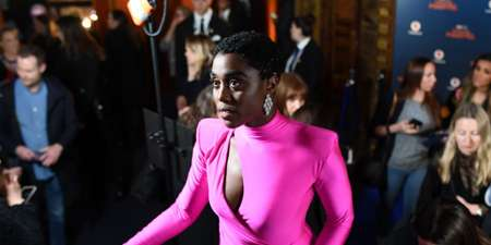 Lashana Lynch at an event wearin a maroon dress without her boyfriend.