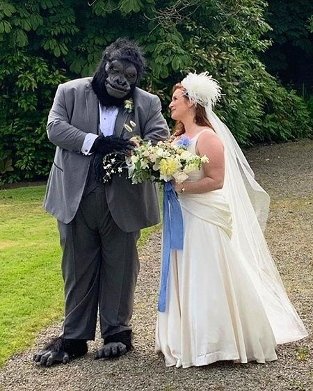 Jorge in a Gorilla costume below his suit while his wife looks at him with a bouquet in his hands.