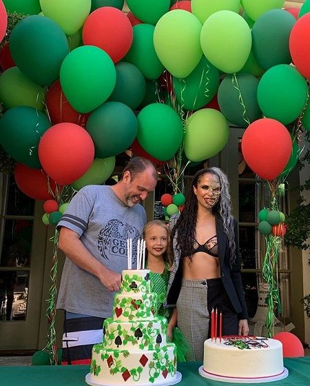Boogie dressed as Batman's nemesis 'Two-Face' (right), Betty as 'Poison Ivy' (center) and trey is just in normal home clothes laughing at something and looking down. The are pictured behind two cakes and balloons in the background.