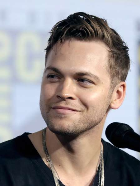 Alexander Calvert answering questions at comic-con while talking about Supernatural.