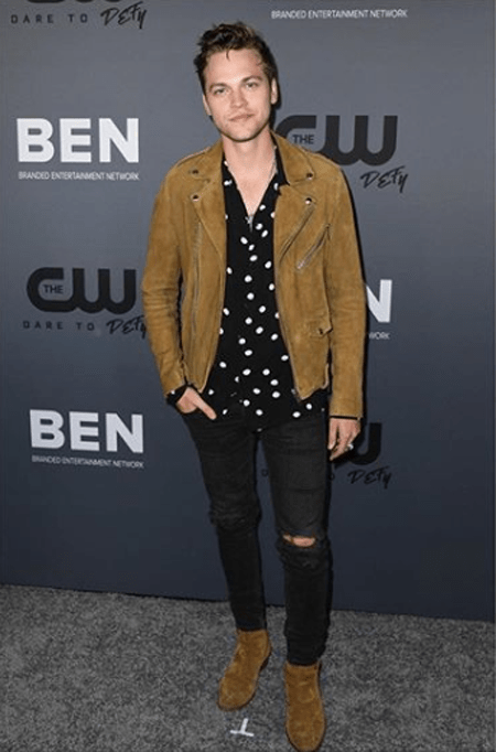 Alexander Calvert in front of The CW banner promoting 'Supernatural.'