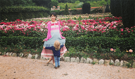 Annet and her daughter in front of a flower garden.