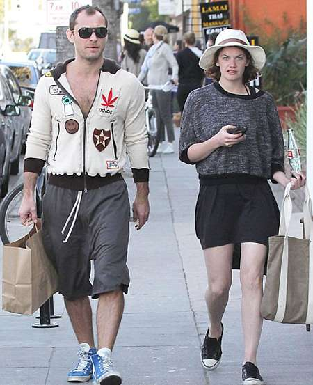 Jude Law and Ruth Wilson walking down the street.