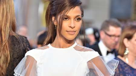 Megalyn Echikunwoke wearing a white top with net arms.