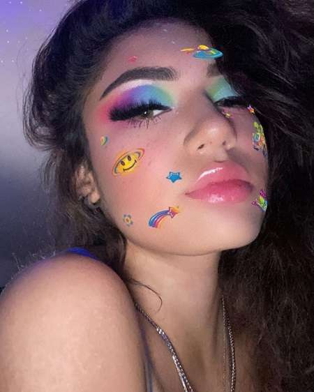 Avani Gregg in a colorful face makeup with cosmos elements.