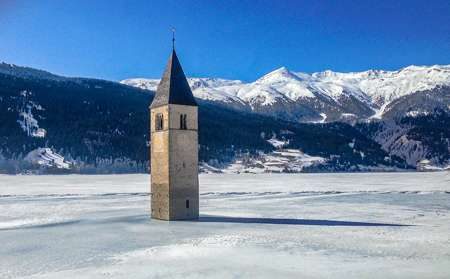 The lake of Curon freezes over during the winter and people can walk up to the base of the bell tower.